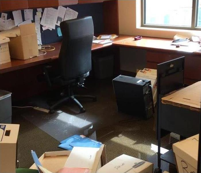 Office with boxes and standing water on carpet floor