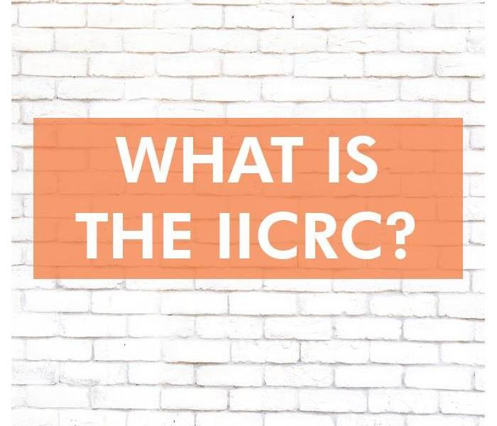 White brick wall with the words WHAT IS THE IICRC