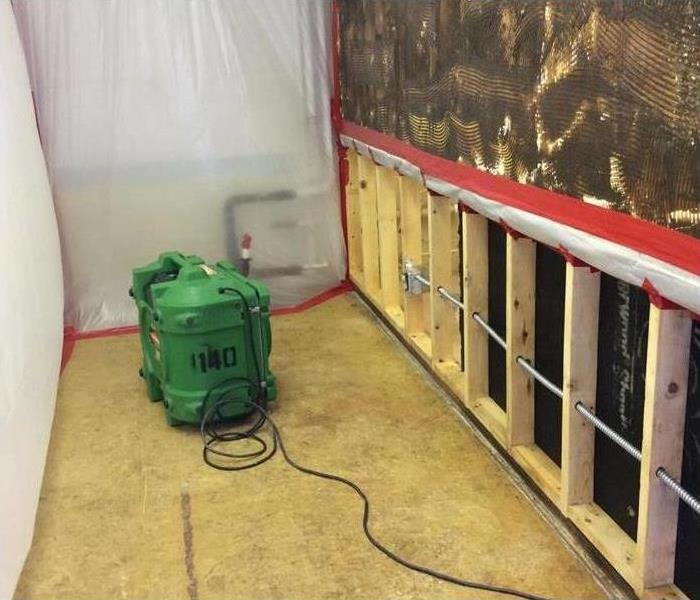 Drywall removed, air scrubber placed on floor, containment barriers placed on wall