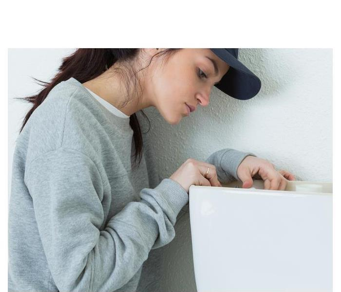 female fixing a toilet