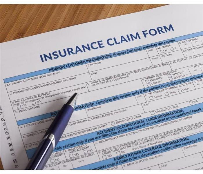 A sheet of an insurance claim for and a pen