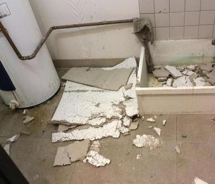 A room with a water heater and broken pieces of tiles on floor